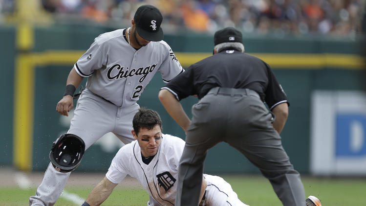 Detroit Tigers' Ian Kinsler slides safely into third base for a triple under the tag of Chicago White Sox third baseman Leury Garcia as third base umpire Tim Timmons looks on in the first inning of a baseball game in Detroit, Thursday, July 31, 2014. (AP Photo/Paul Sancya)