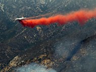 A DC-10 tanker drops fire retardant on a ridge line in the Angeles National Forest, Tuesday, Sept. 4, 2012 near Glendora, Calif. It could be a week before firefighters can contain this 3,600-acre blaze because of high temperatures and rugged terrain in thick brush that hasn't burned in a couple of decades. (AP Photo/Damian Dovarganes)