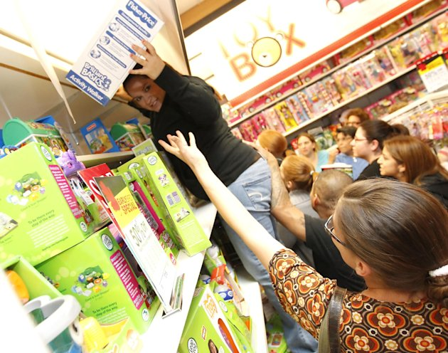 Lorraine Naranjo climbs onto a shelf to get extra Fischer Price walkers shortly after Kohl's opened at midnight on Friday, Nov. 25, 2011, in Corpus Christi, Texas.Black Friday sales began in earne