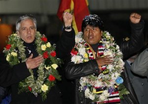 Bolivia's President Evo Morales and Vice President Alvaro Garcia Linera sing the national anthem after Morales' arrival at the El Alto airport on the outskirts of La Paz