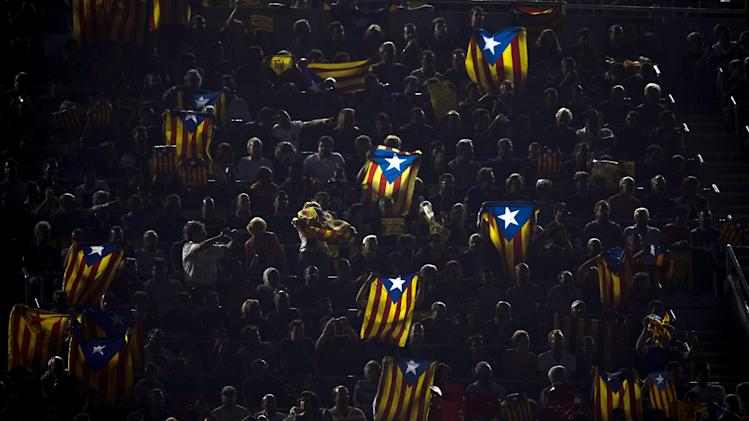 "FILE- In this Oct. 7, 2012, file photo, people hold pro-independence Catalonian flags at the Camp Nou stadium during a Spanish La Liga soccer match between Real Madrid and FC Barcelona in Barcelona, Spain. More than ever, FC Barcelona, known affectionately as Barca, lived up to its motto of being ""more than a club"" for this wealthy northeastern region where Spain's economic crisis is fueling separatist sentiment. Barca has been seen as a bastion of Catalan identity dating back to the three decades of dictatorship when Catalans could not openly speak, teach or publish in their native Catalan language. Barcelona writer Manuel Vazquez Montalban famously called the football team ""Catalonia's unarmed symbolic army.""(AP Photo/Daniel Ochoa De Olza, File)"