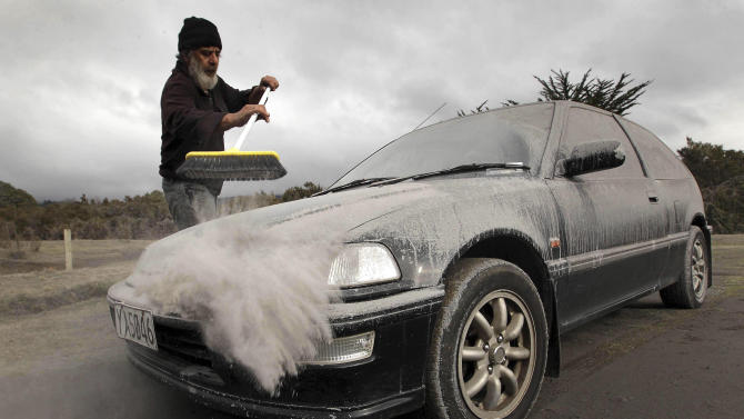 Vic Cassin sweeps ash from a car in Rangipo near Mount Tongariro, New Zealand after an eruption, Tuesday, Aug. 7, 2012. The volcano in New Zealand's central North Island has erupted for the first time in more than a century, sending out an ash cloud that is causing road closures and the cancellation of some domestic flights. (AP Photo/New Zealand Herald, Alan Gibson) AUSTRALIA OUT, NEW ZEALAND OUT