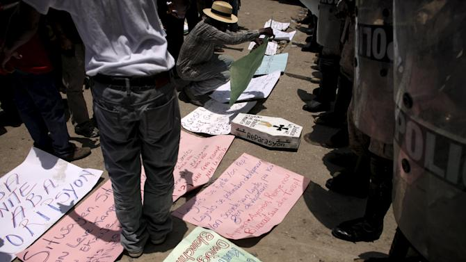 Man arranges placards in front policemen during a protest against what the demonstrators said was corruption in the government, and the release of Woodly Etheart, who was indicted in March on charges that involved kidnapping, in Port-au-Prince