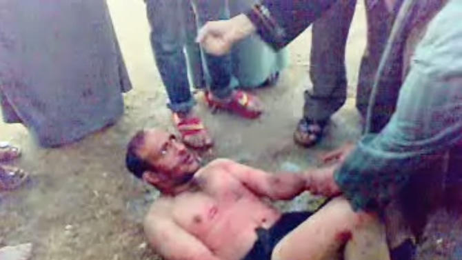 This image made from video, which has been authenticated based on its contents and other AP reporting shows a man, bound by his feet, surrounded by villagers as he asks to be taken to a hospital, before he was beaten and then tied to a tree until he died in the northern Sharqiya province in Egypt, Thursday, March 21, 2013. Egyptian witnesses and officials say villagers beat the man to death after catching him trying to steal a car in a new case of vigilante violence. A number of recent lynchings or attempted lynchings have raised worries over an increasing breakdown of security, adding a new challenge to Egypt's government. A security official says dozens of villagers in Ezbat el-Gindy in the northern Sharqiya province caught the man trying to steal a car at gunpoint Thursday.(AP Photo)
