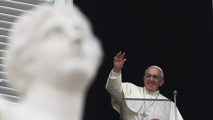 Pope Francis waves as he leads the Angelus prayer from the window of the Apostolic palace at the Vatican