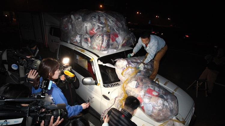 A South Korean worker unloads goods from his vehicle to reload them to another upon arrival from North Korea's Kaesong city at the customs, immigration and quarantine office near the border village of Panmunjom, that has separated the two Koreas since the Korean War, in Paju, South Korea, Tuesday, April 30, 2013. North Korea on Monday approved the withdrawal of most of the remaining South Korean personnel at a jointly run industrial park in the North, South Korean officials said, with a final seven set to stay behind to negotiate unpaid wages for North Korean workers. (AP Photo/Ahn Young-joon)