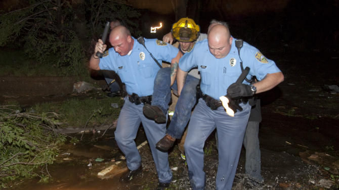 "Sheriff's deputies carry out an injured man from a south Wichita neighborhood after a tornado caused massive destruction in Wichita, Kan., late Saturday, April 14, 2012. Tornadoes were spotted across the Midwest and Plains on Saturday as an outbreak of unusually strong weather seized the region, and forecasters sternly warned that ""life-threatening"" weather could intensify overnight. (AP Photo/The Wichita Eagle, Travis Heying) MAGS OUT; TV OUT"