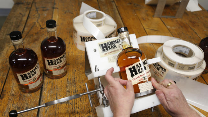 "In this Monday, April 8, 2013 photo Eva Brozovska labels bottles with single malt ""Hammer Head"" whisky in a distillery in Pradlo, Czech Republic. The ""Hammer Head"" whisky made in communist Czechoslovakia matured in oak barrels for more than twenty years to reach surprisingly good quality before hitting the market. (AP Photo/Petr David Josek)"