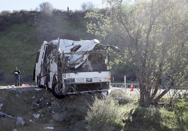 An official takes notes Monday Feb. 4, 2013, at the scene of a tour bus crash near San Bernardino, Calif.  The tour bus carrying dozens of men, women and children from Tijuana, Mexico, crashed in the
