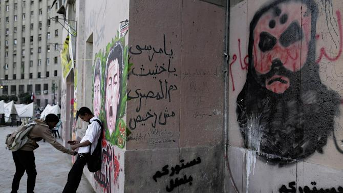 "Egyptian boys stand next to graffiti and Arabic writing on the wall, center, that reads, ""Morsi, Egyptian blood is not cheap,"" in the Tahrir Square in Cairo, Egypt, Sunday, Dec. 9, 2012. Egypt's liberal opposition has called for more protests on Sunday after the president made concessions overnight that fell short of their demands to rescind a draft constitution going to a referendum on Dec. 15. (AP Photo/Hassan Ammar)"
