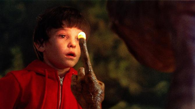 """This undated publicity film image released by Universal Pictures shows Henry Thomas as Elliott and E.T. in a scene from director Steven Spielberg's """"E.T.: The Extra-Terrestrial.""""  In honor of the 30th anniversary of """"E.T.,"""" a digitally remastered feature film returns to theaters Oct. 3, 2012, along with a Blu-ray Anniversary Edition available Oct. 9. (AP Photo/Universal Pictures)"""
