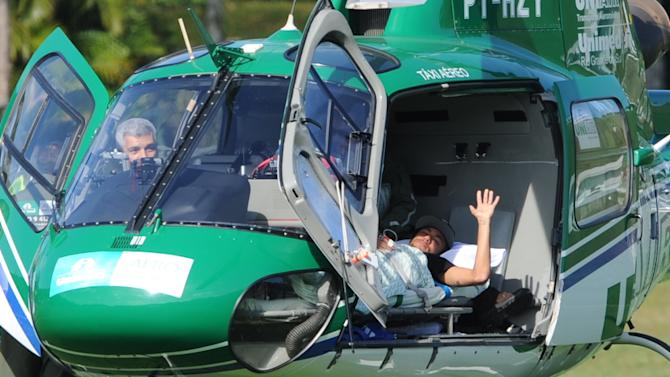 Brazilian striker Neymar waves on July 5, 2014 from inside the helicopter that will transport him from Teresopolis, Rio de Janeiro State, Brazil to his residence in Guaruya