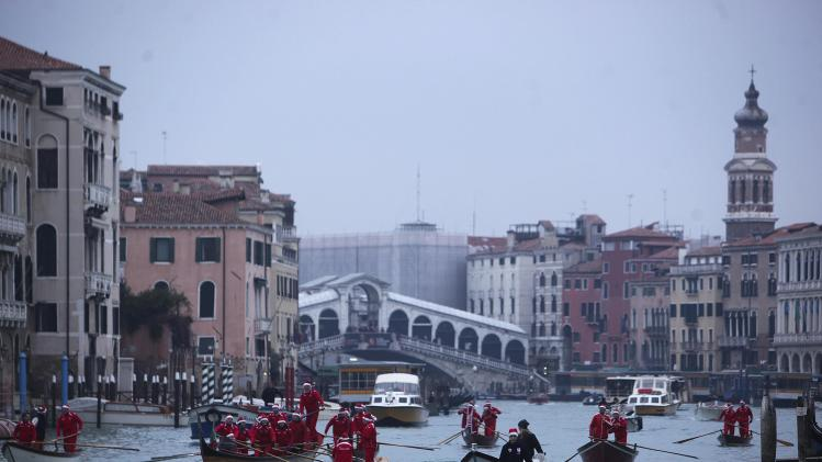 People dressed in Santa Claus costumes row boats on Venice canal