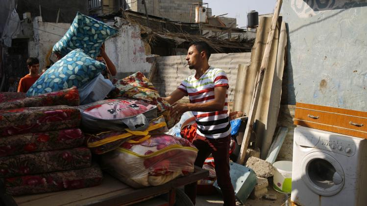 Palestinians salvage materials from a destroyed home in Gaza City