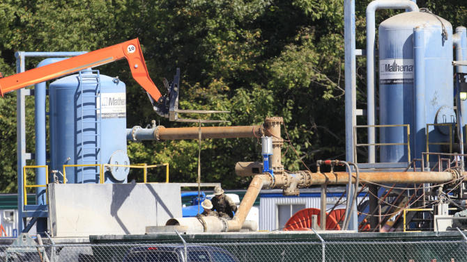 In this Wednesday, Sept. 19, 2012 photo, personnel work on a drill rig in Carrollton, Ohio. Rural Carroll County boasts more active oil and gas wells than any other county in Ohio, and the tax dollars are flowing right along with the crude. (AP Photo/Tony Dejak)