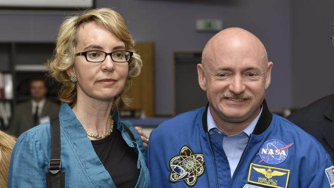 Former U.S. Congresswoman Gabrielle Giffords, left, and her husband Mark Kelly, right, NASA astronaut and commander of mission STS-134, pose for a picture at the Alpha Magnetic Spectrometer (AMS) Payload Operations and Command Center (POCC) at the European Organization for Nuclear Research (CERN) in Meyrin near Geneva, Switzerland, Wednesday, July 25, 2012.  Giffords toured the European particle physics laboratory Wednesday, cheerfully facing reporters while surrounded by family and aides but saying little during her first trip abroad since being shot in the head in January of last year. Two days after riding a cable car up into the French Alps, Giffords accompanied her husband, retired astronaut Mark Kelly, on a visit to the European Center for Nuclear Research, which assembled a  US$2 billion cosmic ray detector that Kelly and his team of astronauts carried to the International Space Station.  (AP Photo/Keystone/Martial Trezzini)