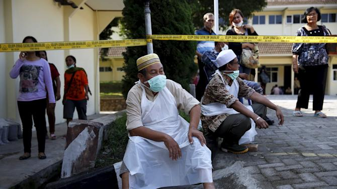 An Indonesian man, Ibrahim, who is in charge of bathing the corpse of the victims of the Indonesian military C-130 Hercules transport plane that crashed into a residential area, rests near the morgue of the Adam Malik hospital in Medan