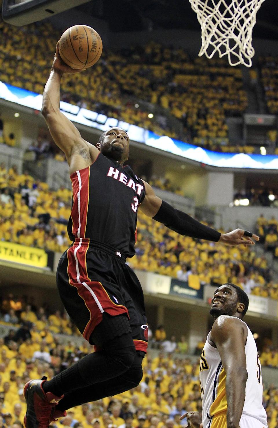 Miami Heat's Dwyane Wade dunks as Indiana Pacers' Roy Hibbert watches during the first half of Game 6 of their NBA basketball Eastern Conference semifinal playoff series, Thursday, May 24, 2012, in Indianapolis. (AP Photo/Darron Cummings)