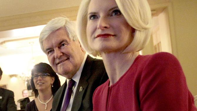 """FILE - In this March 13, 2012 file photo, Jackie Gingrich Cushman, left, sits with her father, Republican presidential candidate, former House Speaker Newt Gingrich and his wife Callista in Birmingham, Ala. Gingrich's daughter says the former House speaker will """"reassess"""" his campaign after the votes are tallied in Delaware, potentially setting the stage for his exit from the Republican presidential race.  (AP Photo/David Goldman)"""