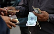 <p>A parking lot employee receives payment from a customer in New Delhi. Kaushik Basu, the government's chief economic advisor says better behaviour such as respecting meeting times and public spaces, as well as more moral behaviour in terms of less cheating or thieving, are both desirable and necessary for economic development</p>