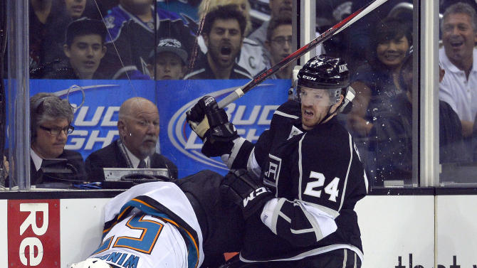 Los Angeles Kings center Colin Fraser, right, checks San Jose Sharks center Tommy Wingels during the first period in Game 2 of a second-round NHL hockey Stanley Cup playoff series, Thursday, May 16, 2013, in Los Angeles.  (AP Photo/Mark J. Terrill)