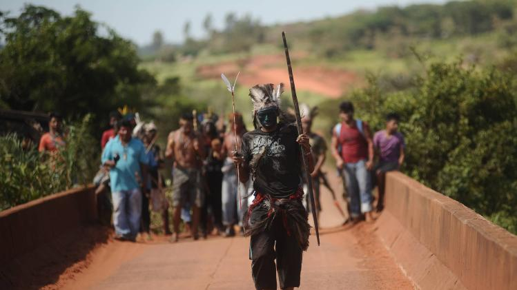 Members of the Guarani Nandeva tribe stand guard at the entrance to one of the 14 farms they have been occupying in Japora
