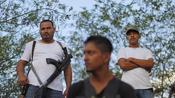 "In this Nov. 5 photo, armed men from to a self-defense group create a checkpoint in the town of Las Colonias, Mexico. Several communities have created their own self-defense groups after a pseudo-religious cartel, known as the ""Knights Templar,"" has for years demanded protection payments from cattlemen, lime growers and other businesses. The groups say they are free of the cartel in several municipalities of the Tierra Caliente, or ""Hot Land,"" which earned its moniker for the scorching weather but whose name has also come to signify criminal activity. (AP Photo/Dario Lopez-Mills)"