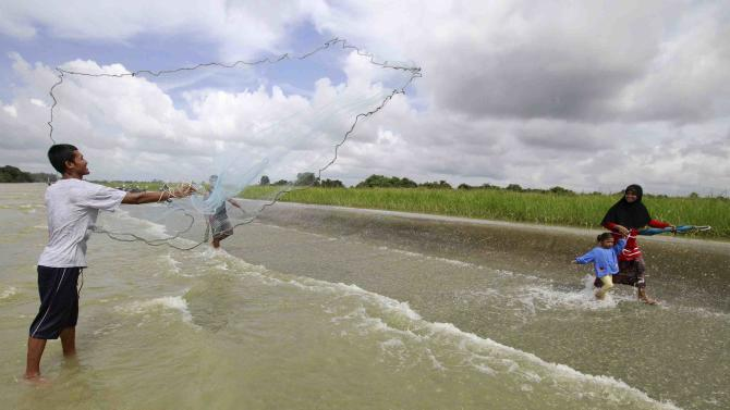 A man casts a fishing net as local residents make their way on a flooded road in the Pattani province