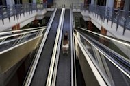 <p>A woman stands on an escalator with her shopping trolley at a partially empty supermarket in Nicosia on June 21. By a cruel twist of fate Cyprus is poised to take the chair as EU president tasked with guiding Europe out of financial chaos just as it becomes the fifth eurozone state to seek a Brussels bailout.</p>