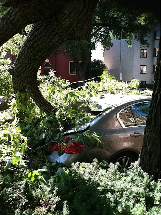 A tree toppled by severe storms sits atop a car in Washington's Dupont Circle neighborhood on Saturday, June 30, 2012 in Washington.  More than two million people across the eastern U.S. lost power af