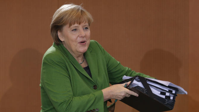 German Chancellor Angela Merkel carries files as she arrives for the weekly cabinet meeting at the chancellery in Berlin, Germany, Wednesday, Nov. 28, 2012. (AP Photo/Michael Sohn)