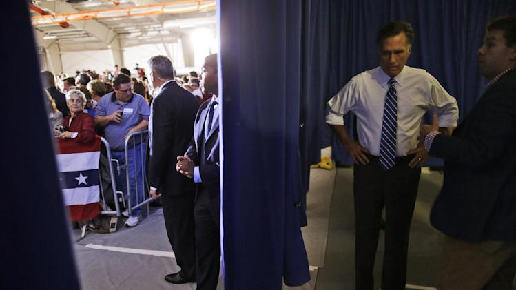 Republican presidential candidate and former Massachusetts Gov. Mitt Romney waits behind a curtain as he is introduced by his vice presidential running mate Rep. Paul Ryan, R-Wis., at a campaign rally at Koehler Athletic Complex, University of Findlay, Sunday, Oct. 28, 2012, in Findlay, Ohio. At right is aide Garrett Jackson. (AP Photo/Charles Dharapak)