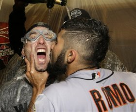 Sergio Romo kisses Marco Scutaro as they are sprayed with celebratory champagne. (AP)