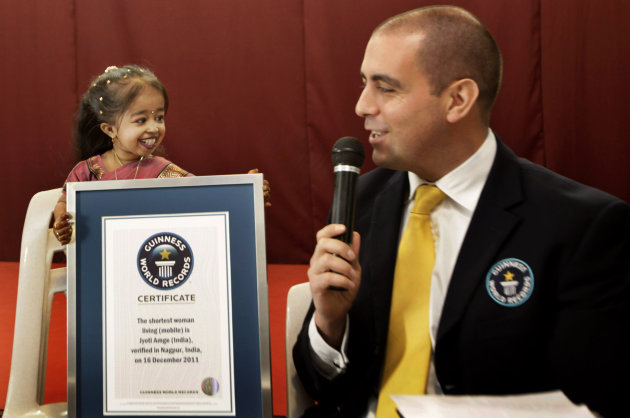 Guinness World Records adjudicator Rob Molloy, right, confers the title of the shortet woman of the world to Jyoti Amge, in Nagpur, India, Friday, Dec. 16, 2011. Amge was declared the shortest woman i