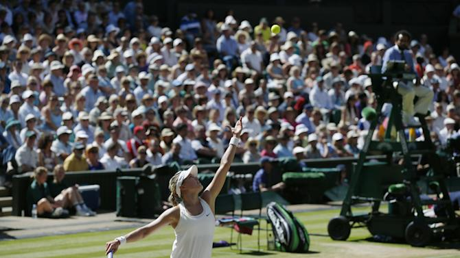 Eugenie Bouchard of Canada serves to Simona Halep of Romania during their women's singles semifinal match at the All England Lawn Tennis Championships in Wimbledon, London, Thursday July 3, 2014. (AP Photo/Pavel Golovkin)