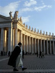 A monk walks across Saint Peter's Square as the sun sets at the Vatican March 16, 2013. REUTERS/Chris Helgren