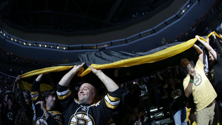 Boston Bruins fans pass a large banner through the stands before Game 3 of the NHL hockey Stanley Cup Finals against the Chicago Blackhawks in Boston, Monday, June 17, 2013. (AP Photo/Elise Amendola)