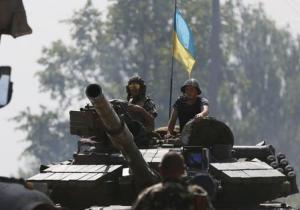 Ukrainian soldiers look out from a tank at a position some 60 km from Donetsk
