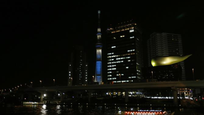Tokyo Sky Tree is pictured behind the Sumida river as a Japanese houseboat passes at Asakusa district in Tokyo