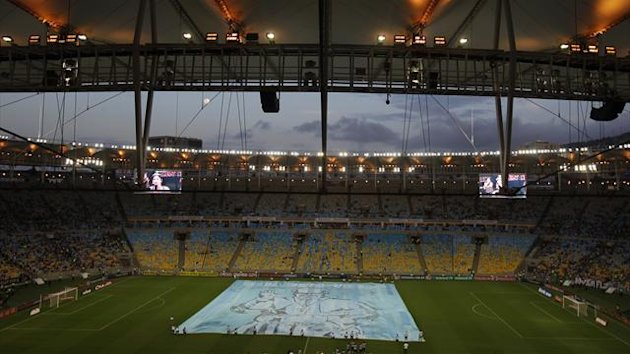 A banner with the Pope's photo is displayed on the field of the Maracana stadium before a game between Fluminense and Vasco da Gama in Rio (Reuters)