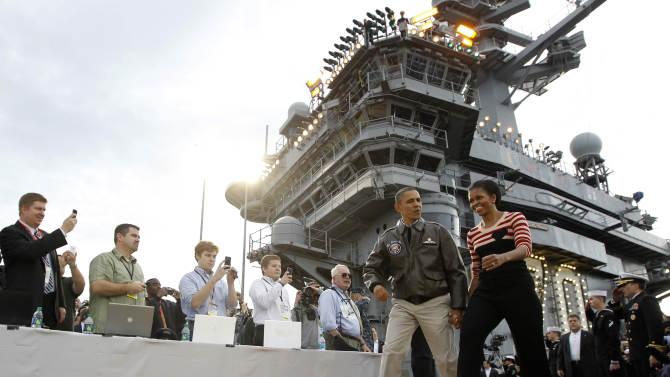 President Barack Obama and first lady Michelle Obama walk on to the basketball court on the flight deck of the USS Carl Vinson during the Carrier Classic NCAA basketball game between Michigan State and North Carolina, Friday, Nov. 11, 2011, in Coronado, Calif. (AP Photo/Charles Dharapak)