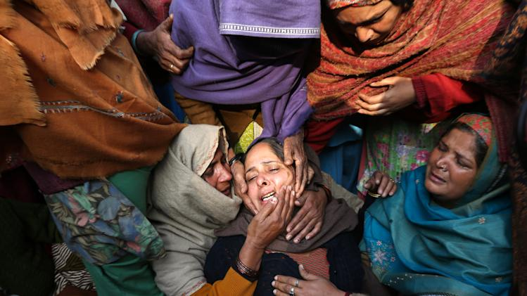 Unidentified women console the wife of Subhash Tomar, a policeman, during his funeral in New Delhi