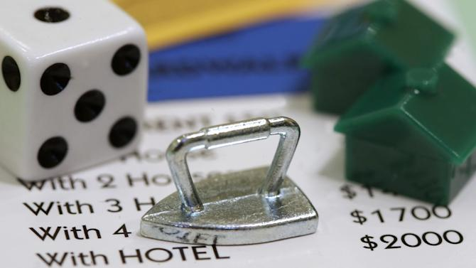 The Monopoly iron token that was replaced by the new cat token rests on a Boardwalk deed next to a die and houses at Hasbro Inc. headquarters in Pawtucket, R.I., Tuesday, Feb. 5, 2013. Hasbro will discontinue the iron after a vote on Facebook determined that the cat would replace it. (AP Photo/Steven Senne)