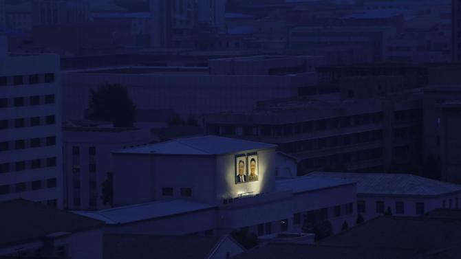 In this Aug. 19, 2015 file photo, portraits of the late North Korean leaders Kim Il Sung, left, and Kim Jong Il glow on the facade of a building among others at dawn in Pyongyang, North Korea. (AP Photo/Dita Alangkara, File)
