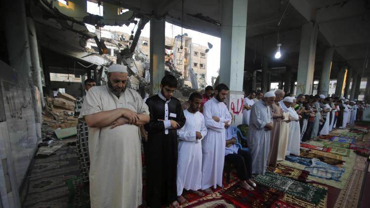 Palestinians perform the Eid al-Fitr prayer at al-Farouk mosque, which witnesses said was hit by an Israeli air strike, in Rafah in the southern Gaza Strip