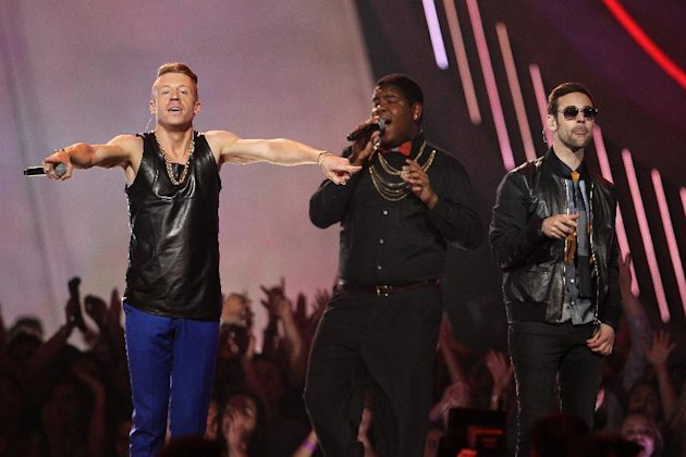 "FILE - This April 14, 2013 file photo shows Macklemore, left, and Ryan Lewis, right, performing ""Can't Hold Us"" with Ray Dalton at the MTV Movie Awards in Sony Pictures Studio Lot in Culver City, Calif. The song was the top streamed track on Spotify from Monday, May 6, to Sunday, May 12. (Photo by Matt Sayles/Invision /AP)"