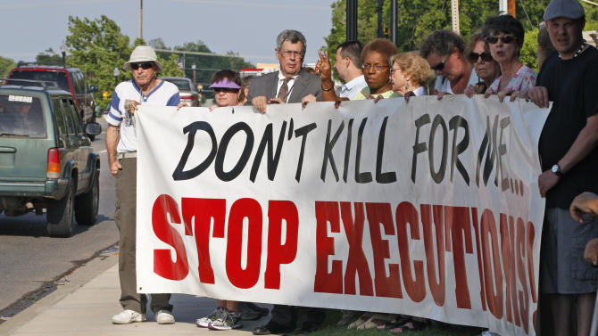 Death penalty opponents hold a sign outside the Governor's Mansion in Oklahoma City, Tuesday, May 1, 2012, to protest the execution of Michael Bascum Selsor. An Oklahoma man convicted of murdering a Tulsa convenience store manager almost 37 years ago was executed by lethal injection Tuesday. (AP Photo/Sue Ogrocki)