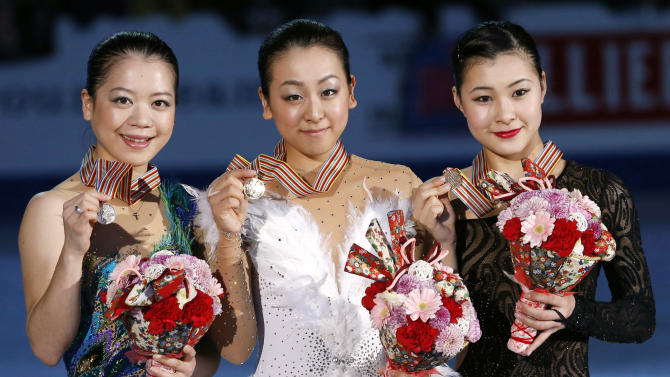 Winner Mao Asada, center, second-placed, Akiko Suzuki, left, and third-placed Kanako Murakami, all of Japan, pose for photographers after the awarding ceremony of women's events of the ISU Four Continents Figure Skating Championships in Osaka, Japan, Sunday, Feb. 10, 2013. (AP Photo/Shizuo Kambayashi)