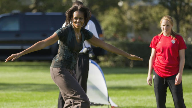 "FILE - In this Oct. 6, 2011, file photo, first lady Michelle Obama plays soccer on the South Lawn of the White House in Washington, as part of a Let's Move! clinic. Michelle Obama has a new look, both in person and online, and with the president's re-election, she has four more years as first lady, too. The first lady is trying to figure out what comes next for this self-described ""mom in chief"" who also is a champion of healthier eating, an advocate for military families, a fitness buff and the best-selling author of a book about her White House garden. For certain, she'll press ahead with her well-publicized efforts to reduce childhood obesity and rally the country around its service members. (AP Photo/Evan Vucci, File)"