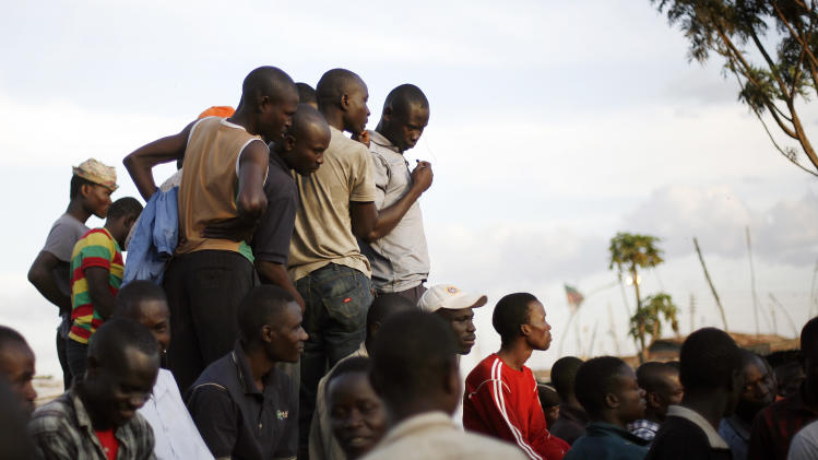 "Young men listen to others debating elections in  the Kibera slum of Nairobi, Kenya, Thursday, March 7, 2013. Kenyans on Monday held their first presidential vote since the nation's disputed election in 2007 spawned violence that killed more than 1,000 people. The coalition of Kenya's prime minister Raila Odinga says the vote tallying process now under way to determine the winner of the country's presidential election ""lacks integrity"", should be stopped, and the counting process should be restarted using primary documents from polling stations. (AP Photo/Jerome Delay)"